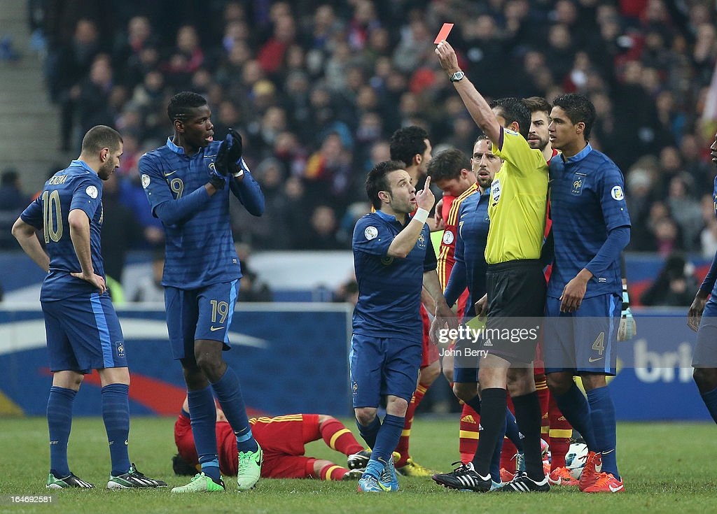 Paul Pogba of France gets a red card from referee Viktor Kassai while Mathieu Valbuena, Raphael Varane look on during the FIFA World Cup 2014 qualifier match between France and Spain at the Stade de France on March 26, 2013 in Saint-Denis near Paris, France.
