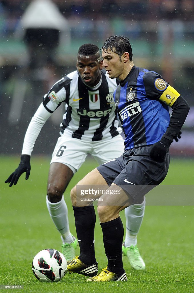 Paul Pogba of Juventus FC #6 and Javier Zanetti of FC Inter Milan compete for the ball during the Serie A match between FC Internazionale Milano and Juventus FC at San Siro Stadium on March 30, 2013 in Milan, Italy.