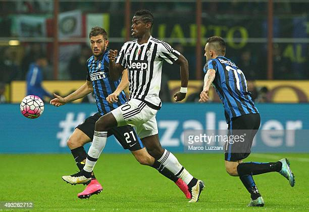 Paul Pogba of Juventus FC competes for the ball with Davide Santon and Marcelo Brozovic of FC Internazionale Milano during the Serie A match between...