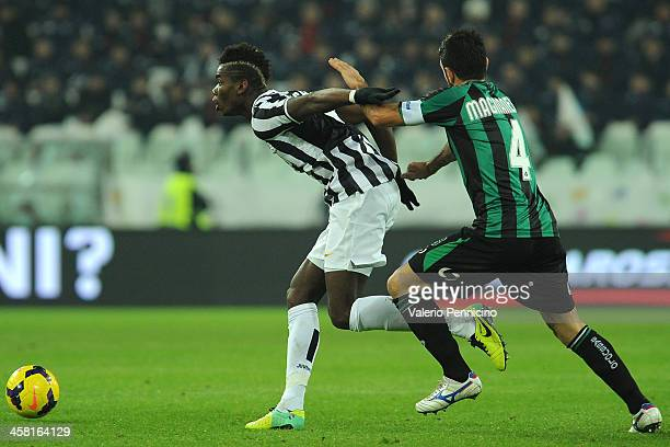 Paul Pogba of Juventus is challenged by Francesco Magnanelli of US Sassuolo Calcio during the Serie A match between Juventus and US Sassuolo Calcio...