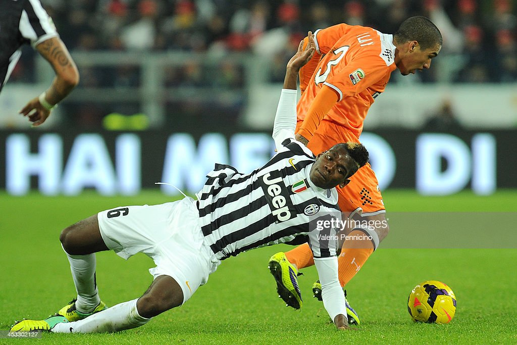 Paul Pogba (L) of Juventus is tackled by Allan Marques of Udinese Calcio during the Serie A match between Juventus and Udinese Calcio at Juventus Arena on December 1, 2013 in Turin, Italy.