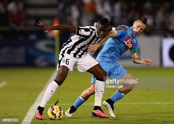 Paul Pogba of Juventus is tackled by Marek Hamsik of Napoli during the 2014 Italian Super Cup match between Juventus FC v SSC Napoli at the Jassim...
