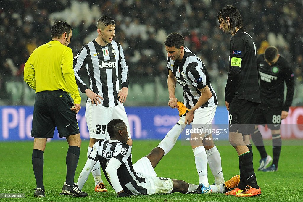 Paul Pogba (L) of Juventus receives treatment from his team-mates Leonardo Bonucci during the UEFA Champions League round of 16 second leg match between Juventus and Celtic at Juventus Arena on March 6, 2013 in Turin, Italy.