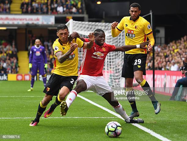 Paul Pogba of Manchester United battles with Jose Holebas and Etienne Capoue of Watford during the Premier League match between Watford and...