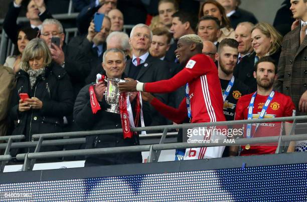 Paul Pogba of Manchester United hands the trophy to Jose Mourinho Manager of Manchester United during the EFL Cup Final match between Manchester...