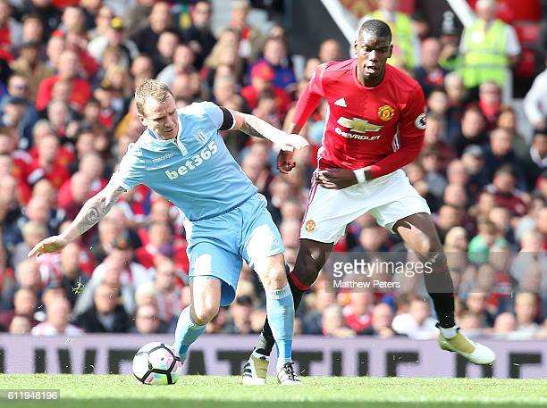Paul Pogba of Manchester United in action with Glenn Whelan of Stoke City during the Premier League match between Manchester United and Stoke City at...