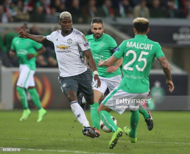 Paul Pogba of Manchester United in action with Kevin Malcuit of AS SaintEtienne during the UEFA Europa League Round of 32 second leg match between AS...