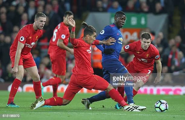 Paul Pogba of Manchester United in action with Roberto Firmino and James Milner of Liverpool during the Premier League match between Liverpool and...