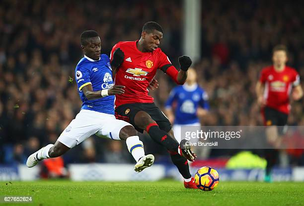 Paul Pogba of Manchester United is challenged by Idrissa Gueye of Everton during the Premier League match between Everton and Manchester United at...