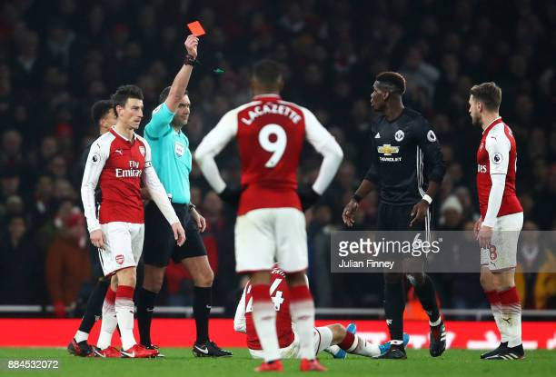 Paul Pogba of Manchester United is shown a red card by referee Andre Marriner for stamping on Hector Bellerin of Arsenal during the Premier League...