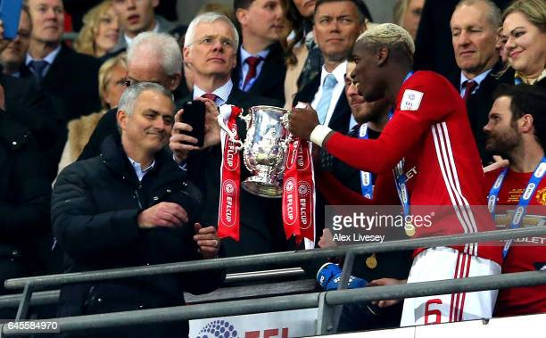 Paul Pogba passes the trophy to Jose Mourinho manager of Manchester United in victory after during the EFL Cup Final between Manchester United and...