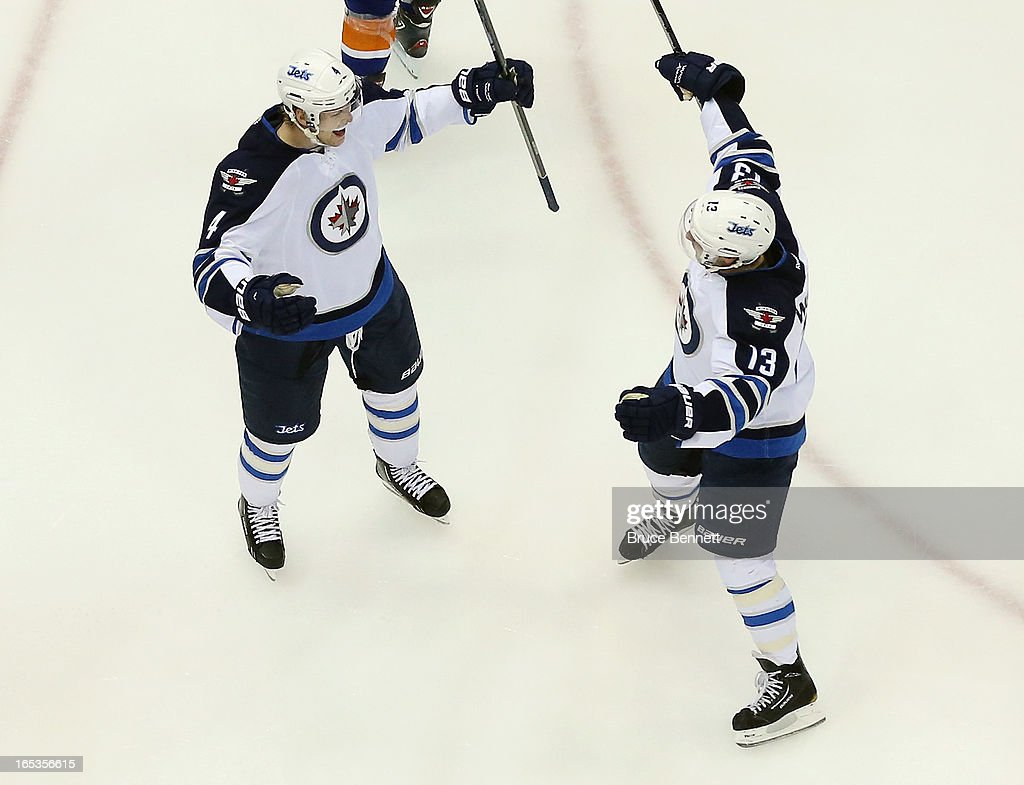 Paul Postma #4 and Kyle Wellwood #13 of the Winnipeg Jets celebrate a goal against the New York Islanders at the Nassau Veterans Memorial Coliseum on April 2, 2013 in Uniondale, New York. The Islanders defeated the Jets 5-2.