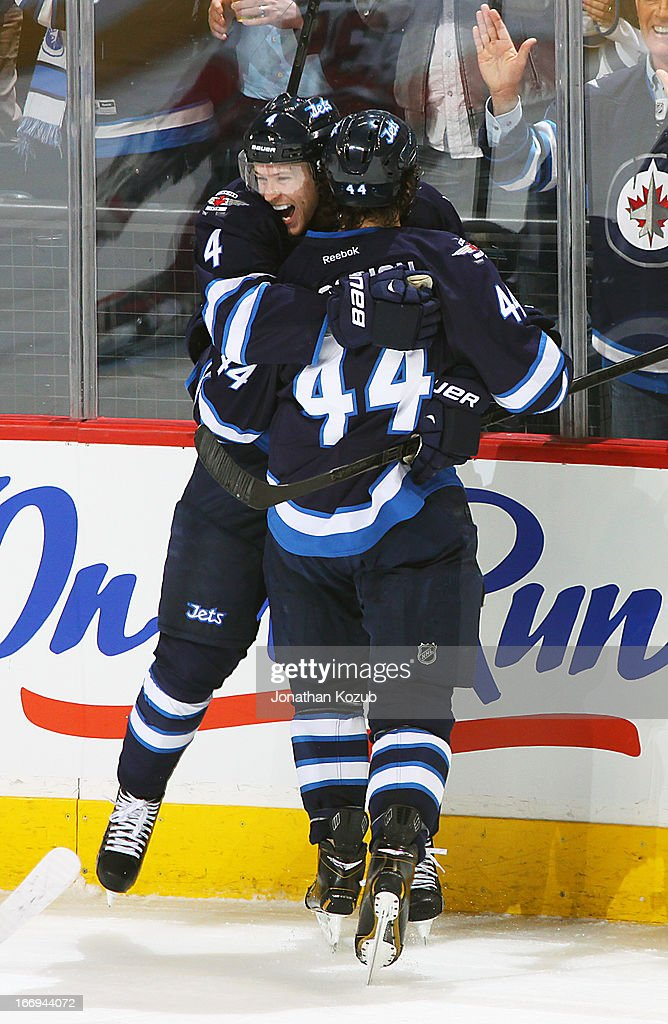 Paul Postma #4 and Zach Bogosian #44 of the Winnipeg Jets embrace as they celebrate a second period goal against the Carolina Hurricanes at the MTS Centre on April 18, 2013 in Winnipeg, Manitoba, Canada.