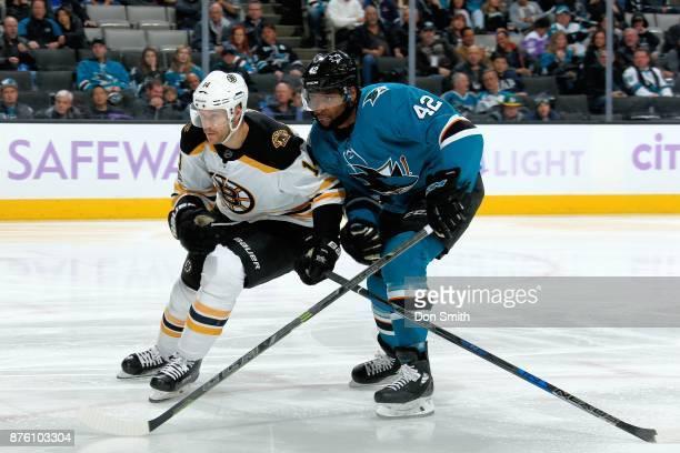Paul Postma of the Boston Bruins and Joel Ward of the San Jose Sharks jostle for position at SAP Center on November 18 2017 in San Jose California