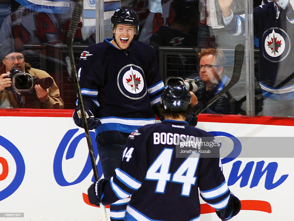 Paul Postma #4 of the Winnipeg Jets is all smiles as teammate Zach Bogosian #44 joins him to celebrate his second period goal against the Carolina Hurricanes at the MTS Centre on April 18, 2013 in Winnipeg, Manitoba, Canada.