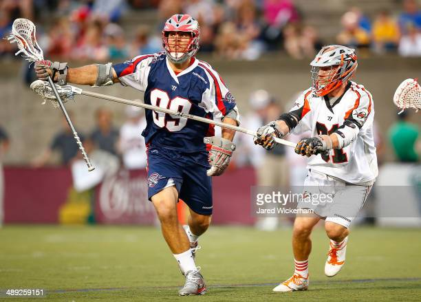 Paul Rabil of the Boston Cannons runs downfield with the ball in the first half past Dillon Roy of the Denver Outlaws at Harvard Stadium on May 10...