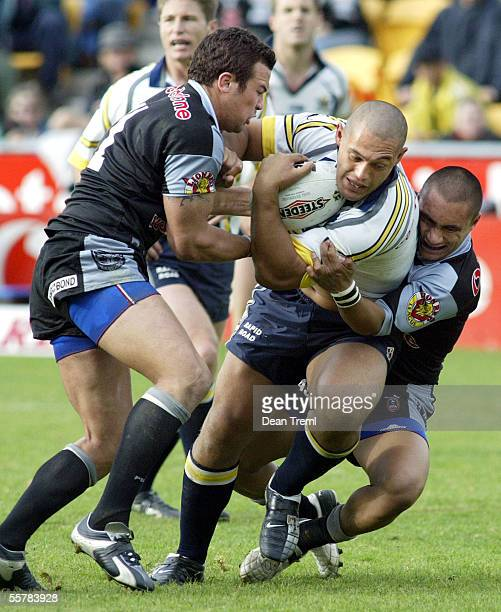Paul Rauhihi of the Cowboys is tackled by Louis Anderson and Thomas Leuluai of the Warriors during Round 15 of the NRL Rugby League between the New...