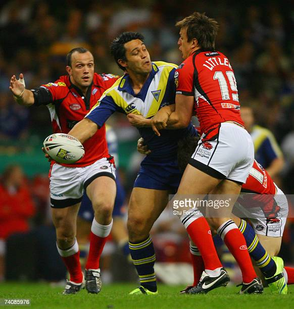 Paul Rauhihi of the Wolves offloads as he is tackled by Stuart Littler of the Reds during the Engage Super League match between Salford Reds and...