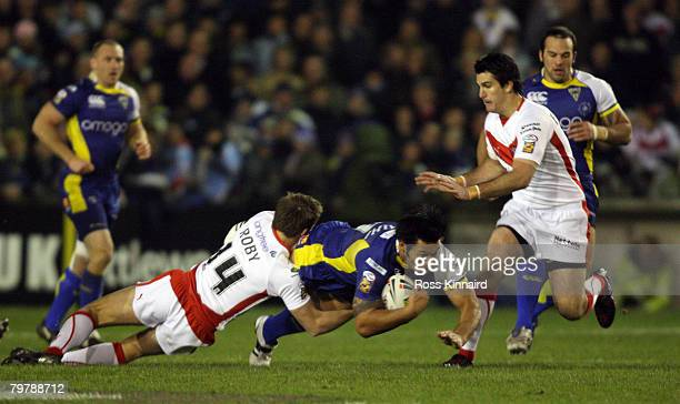 Paul Rauhihi of Warrington is tackled by James Roby of St Helens during the Super Leaue match between St Helens and Warrington Wolves at the Knowsley...