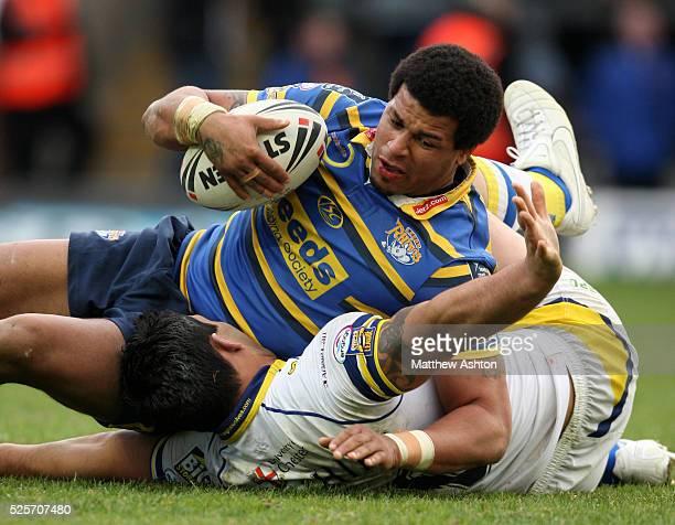 Paul Rauhihi of Warrington Wolves tries to stop Ryan Bailey of Leeds Rhinos