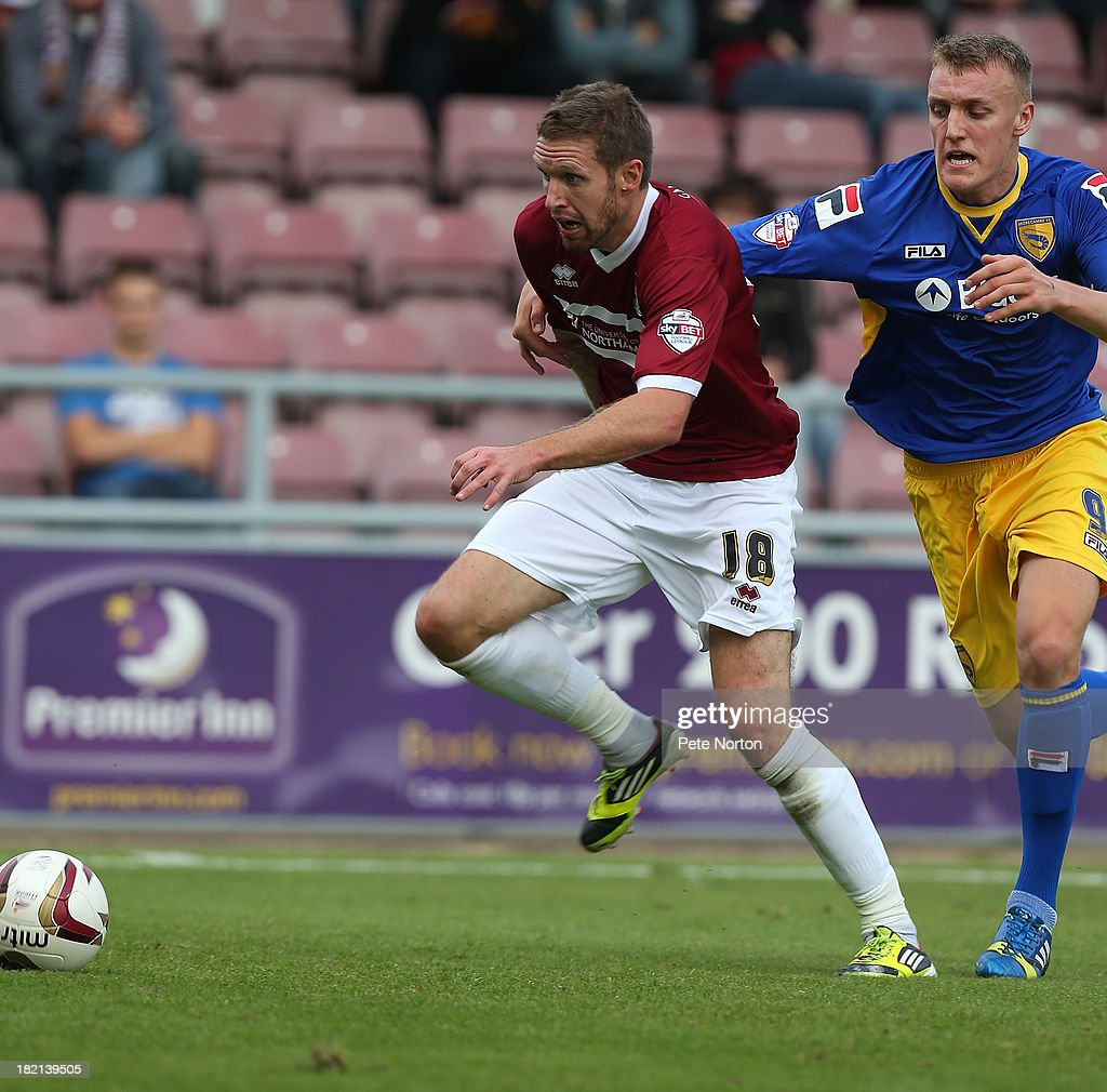 Paul Reid of Northampton Town moves away with the ball from Jack Sampson of Morecambe during the Sky Bet League Two match between Northampton Town and Morecambe at Sixfields Stadium on September 28, 2013 in Northampton, England.
