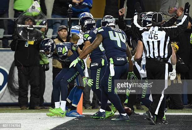 Paul Richardson of the Seattle Seahawks celebrates with teammates after making a touchdown catch against Tavon Wilson of the Detroit Lions during the...