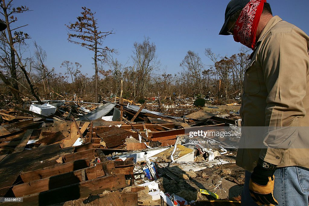 Paul Rovane stands on the roof of his friends mothers home destroyed by Hurricane Katrina September 8 2005 in Waveland Mississippi Thousands of...