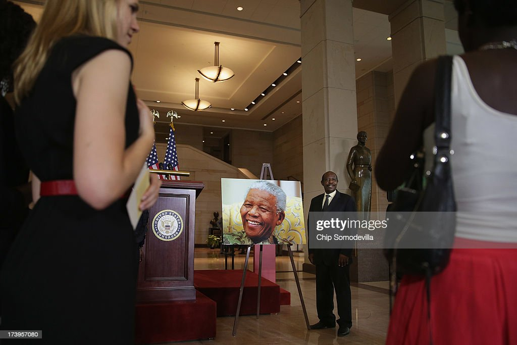 Paul Rusesabagina, the Rwandan hotel manager and humanitarian who hid and protected 1,268 refugees during the Rwandan Genocide, poses for photos with an image of Nobel Peace Prize laureate and former South Africa President Nelson Mandela before a ceremony to celebrate Mandela on his 95th birthday in the U.S. Capitol Visitor Center July 18, 2013 in Washington, DC. July 18 is Nelson Mandela Day, during which people are asked to give 67 minutes of time to charity and service in their community to honor the 67 years Mandela gave to public service. Mandela was admitted to a South African hospital June 8 where he is being treated for a recurring lung infection.