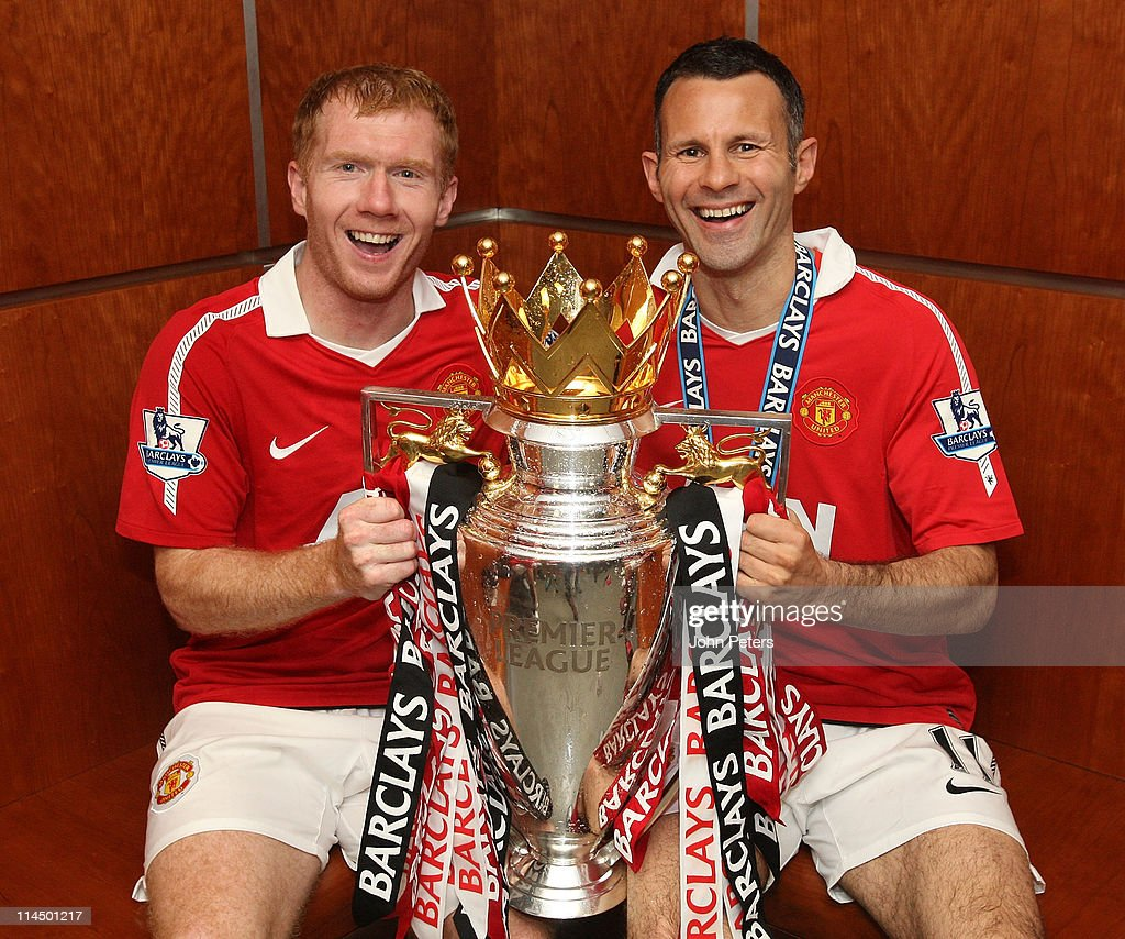 Paul Scholes and Ryan Giggs of Manchester United pose in the dressing room with the Barclays Premier League trophy after the Barclays Premier League match between Manchester United and Blackpool at Old Trafford on May 22, 2011 in Manchester, England.