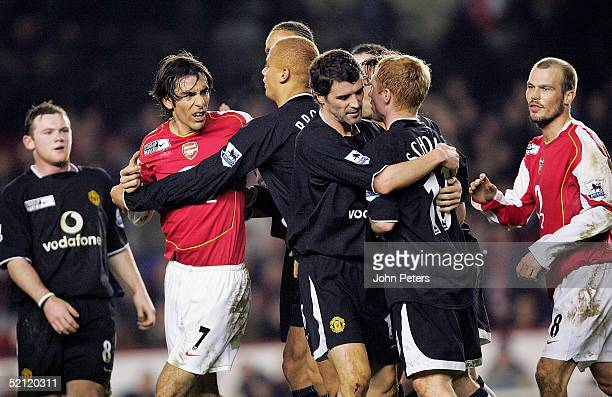 Paul Scholes of Manchester United clashes with Robert Pires of Arsenal during the Barclays Premiership match between Arsenal and Manchester United at...