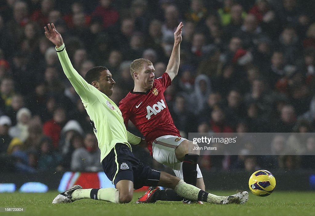 Paul Scholes of Manchester United in action with James Perch of Newcastle United during the Barclays Premier League match between Manchester United and Newcastle United at Old Trafford on December 26, 2012 in Manchester, England.