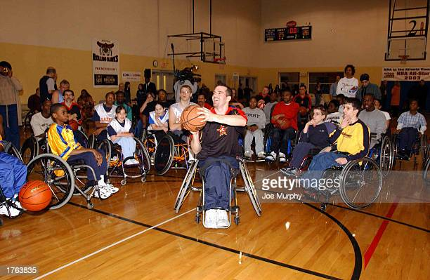 Paul Schulte of the NWBA AllStars shows kids how to shoot properly at a Wheelchair Youth Clinic at the Marcus Jewish Community Center on February 5...
