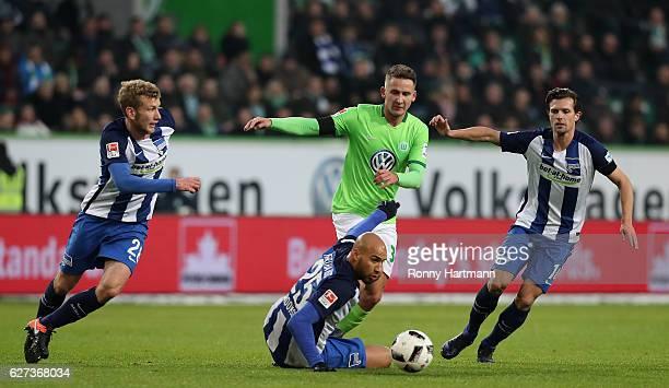 Paul Seguin of Wolfsburg vies with Fabian Lustenberger John Anthony Brooks and Valentin Stocker of Berlin during the Bundesliga match between VfL...