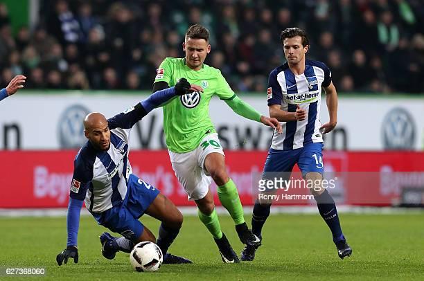 Paul Seguin of Wolfsburg vies with John Anthony Brooks and Valentin Stocker of Berlin during the Bundesliga match between VfL Wolfsburg and Hertha...