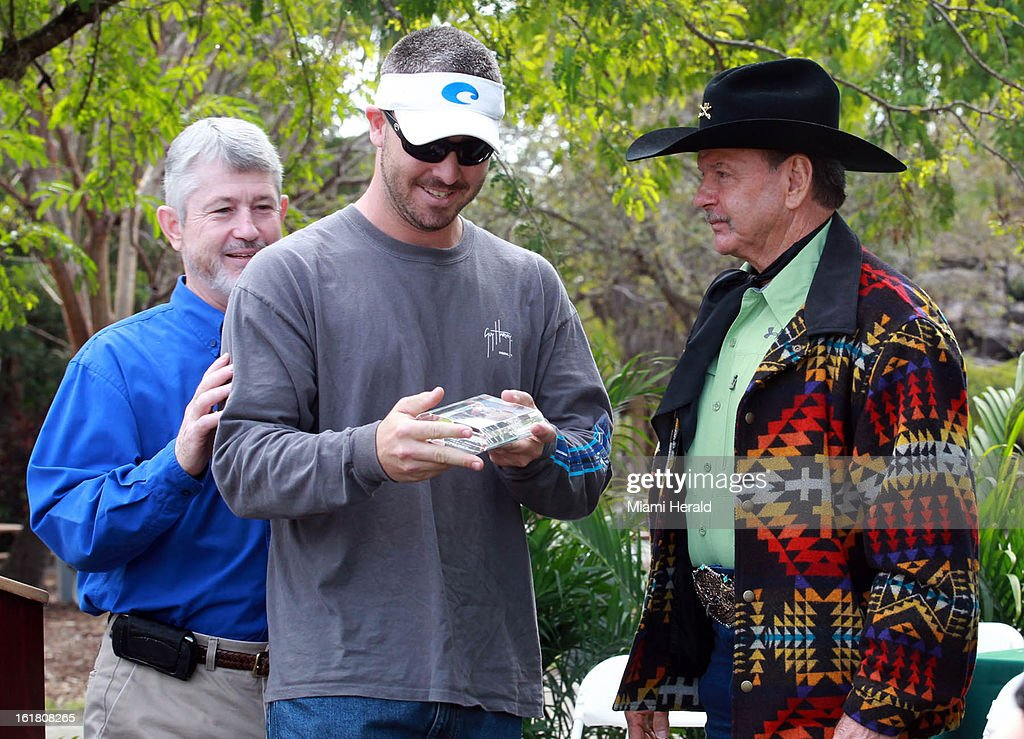 Paul Shannon, center, received his award for longest python caught by an unlicensed hunter, (14 feet, 3 inches), during the Python Ceremony held by the Florida Fish and Wildlife Conservation Commission at Zoo Miami, in Miami, Florida, Saturday, February 16, 2013.