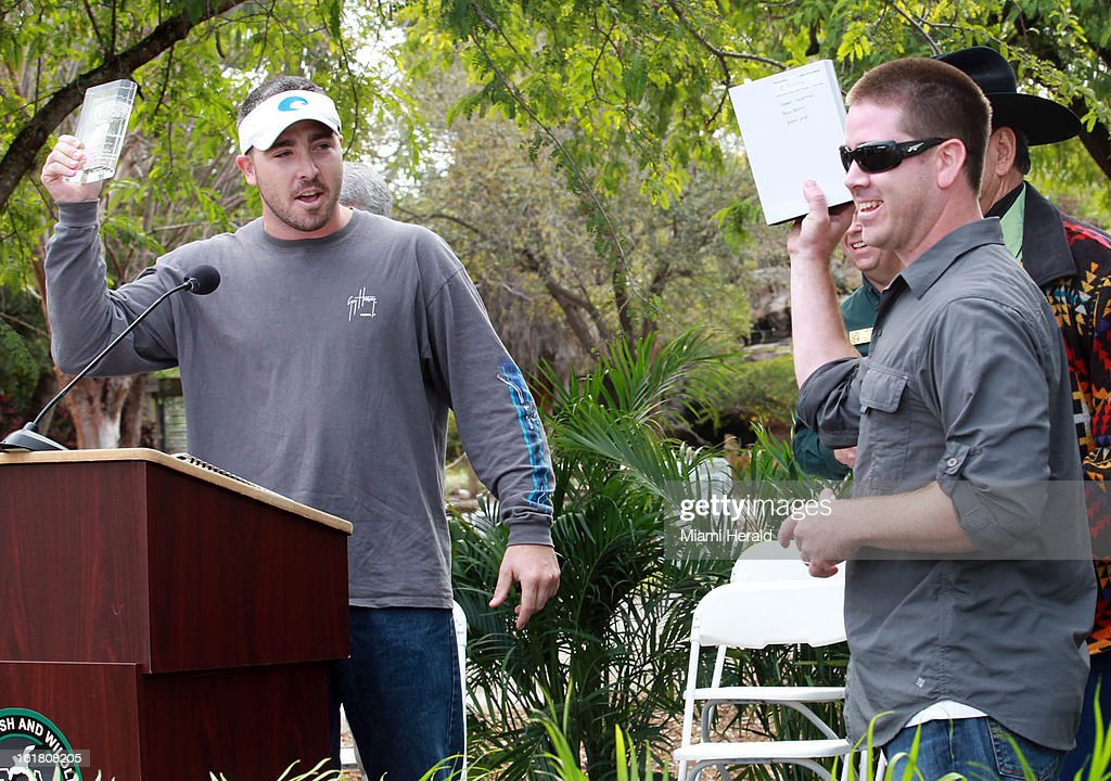Paul Shannon, left, received his award for longest python caught by an unlicensed hunter (14 feet, 3 inches) and Brian Barrows, for the most pythons caught, which was six, during the python hunt awards ceremony conducted by the Florida Fish and Wildlife Conservation Commission at Zoo Miami, in Miami, Florida, Saturday, February 16, 2013.