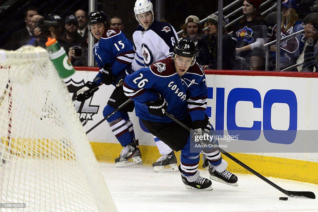 Paul Stastny (26) of the Colorado Avalanche controls the puck as Jacob Trouba (8) of the Winnipeg Jets defends P.A. Parenteau (15) of the Colorado Avalanche during the first period of action. The Colorado Avalanche hosted the Winnipeg Jets at the Pepsi Center on Sunday, December 29, 2013.