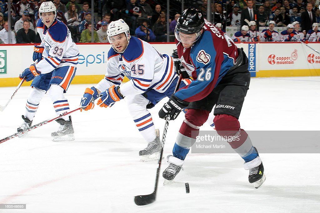Paul Stastny #26 of the Colorado Avalanche tries to control the puck against Mark Fistric #45 and Ryan Smyth #94 of the Edmonton Oilers at the Pepsi Center on February 2, 2013 in Denver, Colorado.