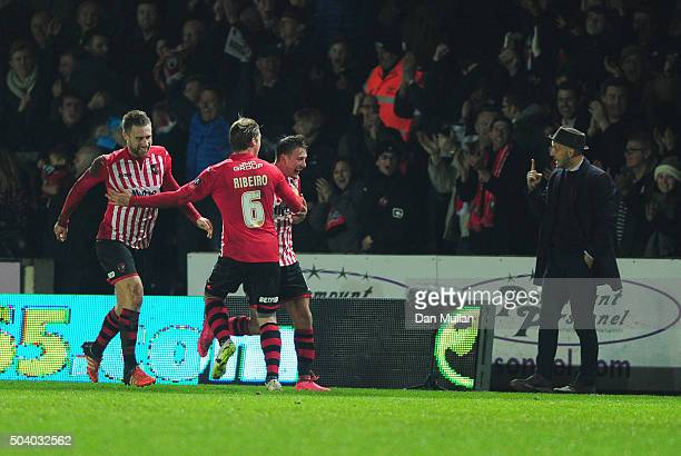 Paul Tisdale manager of Exeter City signals as Lee Holmes of Exeter City celebrates with team mates as he scores their second goal during the...