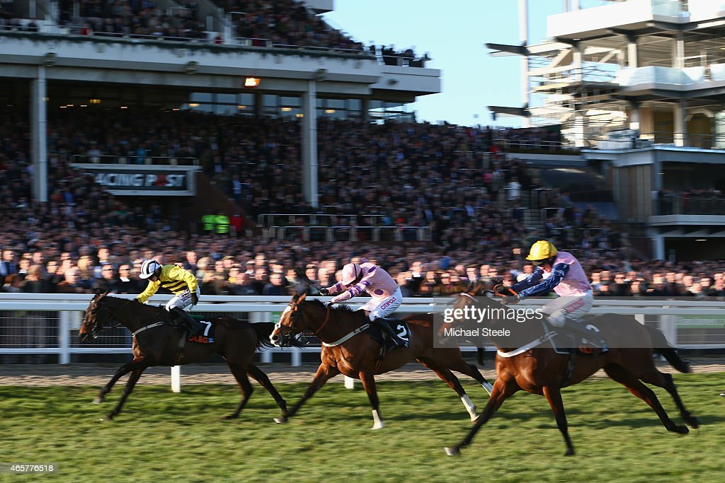 Paul Townend (L) riding Glens Melody on his way to victory from Noel fehily (C) riding Bitofapuzzle and Barry Geraghty (R) riding Polly Peachum in the Olbg Mares' Hurdle Race on day one at Cheltenham Racecourse on March 10, 2015 in Cheltenham, England.