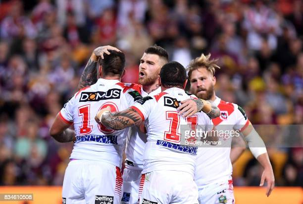 Paul Vaughan of the Dragons is congratulated by team mates after scoring a try during the round 24 NRL match between the Brisbane Broncos and the St...
