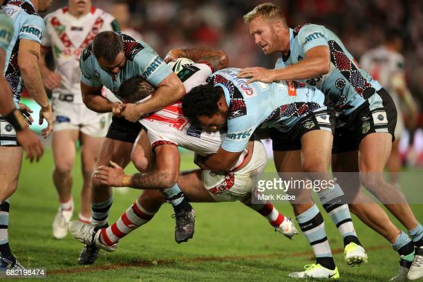 Paul Vaughan of the Dragons is tackled by Wade Graham Joseph Paulo and Matt Prior of the Sharks during the round 10 NRL match between the St George...