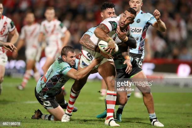 Paul Vaughan of the Dragons passes as he is tackled to Russell Packer of the Dragons to score a try during the round 10 NRL match between the St...