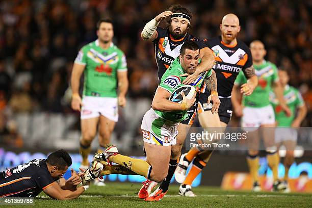 Paul Vaughan of the Raiders is tackled by Sauaso Sue and Aaron Woods of the Tigers during the round 16 NRL match between the Wests Tigers and the...