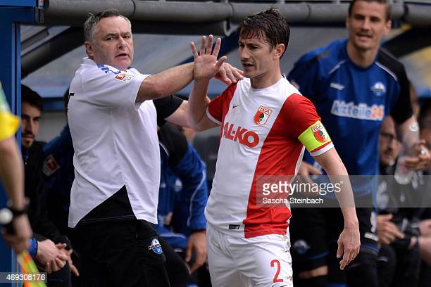 Paul Verhaegh of Augsburg wrangles with kit manager Michael Heppner of Paderborn during the Bundesliga match between SC Paderborn 07 and FC Augsburg...