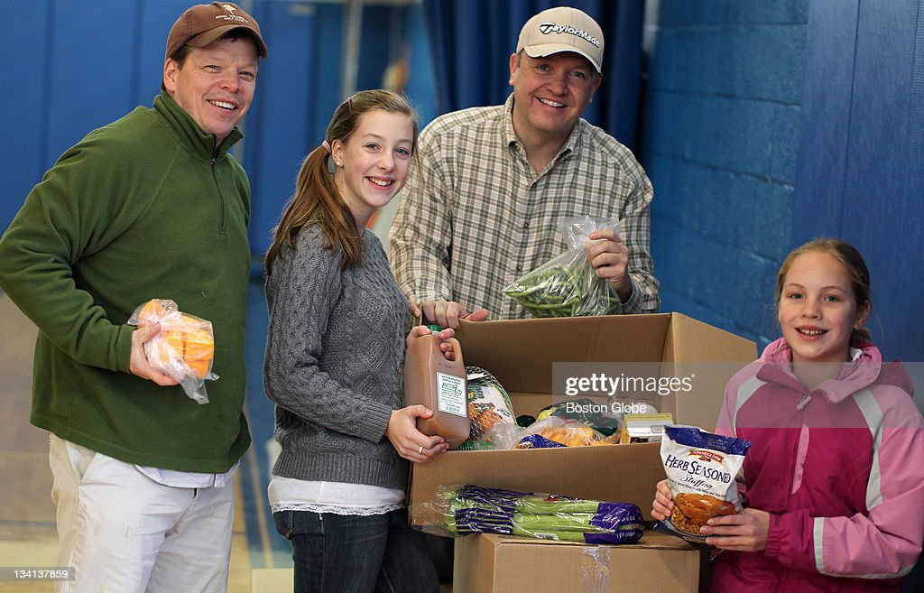 Paul Wahlberg, left, his daughter Madison Wahlberg, his business partner Ed St. Croix and daughter Tiffany St. Croix. Madison and Tiffany have spent the last year raising money through the Alma's kid's charity (named for Paul Wahlberg's mother Alma), to provide turkey dinners. They were loading the last of the boxed dinners in Hingham to distribute to various programs.