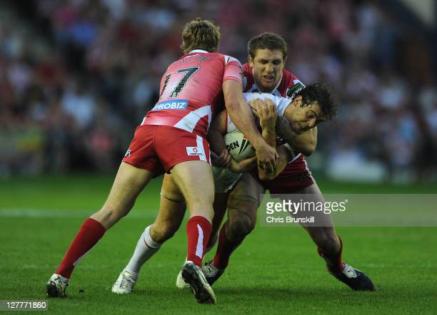 Paul Wellens of St Helens is tackled by Brett Finch and Michael Mcllorum of Wigan Warriors during the Engage Super League Play Off match between St...