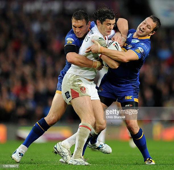 Paul Wellens of St Helens is tackled by Kevin Sinfield and Danny McGuire of Leeds Rhinos during the Engage Super League Grand Final match between St...