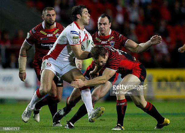 Paul Wellens of St Helens is tackled by Michael Monaghan of Warrington during the Stobart Super League play off match between St Helens and...