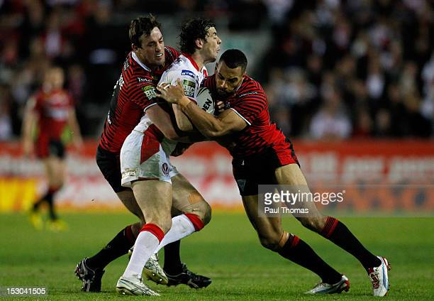 Paul Wellens of St Helens is tackled by Trent Waterhouse and Ryan Atkins of Warrington during the Stobart Super League play off match between St...